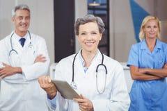 Docteur gai tenant le comprimé numérique tandis que les collègues avec des bras croisaient photos stock