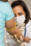 Docteur Giving un projectile dans la verticale de bras Image libre de droits