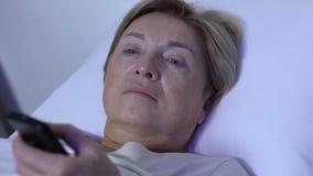 Docteur grossier prenant à TV le contrôleur à distance du vieux patient féminin, manque de respect banque de vidéos