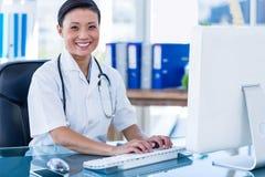 Docteur heureux à l'aide de son ordinateur et regardant l'appareil-photo photos libres de droits