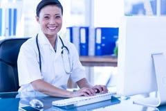 Docteur heureux à l'aide de son ordinateur et regardant l'appareil-photo Photographie stock libre de droits