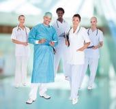 Docteur heureux dans la robe chirurgicale avec ses collègues Image stock
