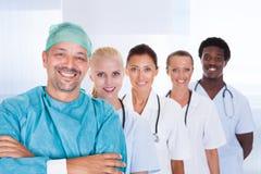 Docteur heureux dans la robe chirurgicale avec ses collègues Images stock