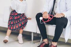 Docteur heureux de visite de petit enfant dans le bureau d'h?pital photo libre de droits