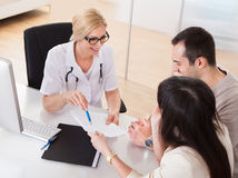 Docteur heureux Discussing With Couple Photographie stock