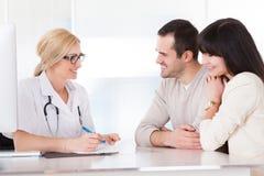 Docteur heureux Discussing With Couple Photos libres de droits