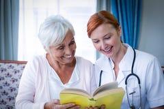 Docteur heureux et patient lisant un livre images libres de droits
