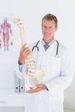 Docteur heureux montrant l'épine anatomique Photographie stock libre de droits