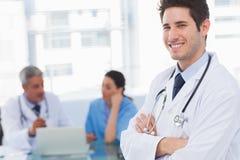 Docteur heureux regardant l'appareil-photo avec des collègues derrière Image libre de droits