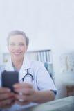 Docteur heureux regardant l'appareil-photo et à l'aide de son smartphone Images stock