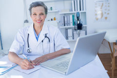 Docteur heureux regardant l'appareil-photo et écrivant sur le presse-papiers Images stock