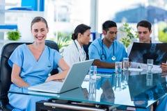 Docteur heureux regardant l'appareil-photo tandis que ses collègues regarde le rayon X Photographie stock libre de droits