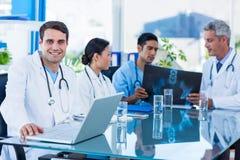 Docteur heureux regardant l'appareil-photo tandis que ses collègues regarde le rayon X Image libre de droits