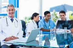 Docteur heureux regardant l'appareil-photo tandis que ses collègues regarde le rayon X Photo libre de droits