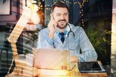 Docteur heureux riant tout en parlant au téléphone avec un ami Photos stock