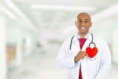 Docteur heureux tenant le coeur rouge se tenant dans le couloir d'hôpital Photographie stock libre de droits