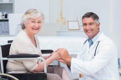 Docteur heureux tenant les mains supérieures de patients photographie stock