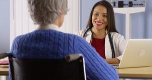 Docteur hispanique heureux parlant avec le patient supérieur photographie stock libre de droits