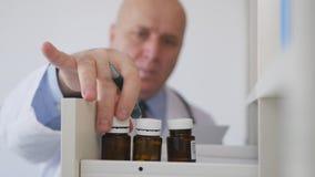 Docteur Image dans le Cabinet médical prenant pour un traitement médical une bouteille de médecine image stock