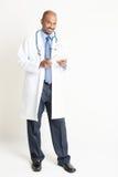 Docteur indien mûr intégral utilisant la tablette photographie stock