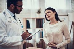 Docteur indien voyant des patients dans le bureau Le docteur écoute les symptômes de la femme L'estomac de la femme blesse images libres de droits