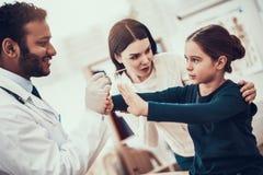 Docteur indien voyant des patients dans le bureau Le docteur essaye d'examiner la gorge de la fille mais la fille refuse photos libres de droits