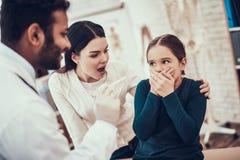 Docteur indien voyant des patients dans le bureau Le docteur essaye d'examiner la gorge de la fille mais la fille refuse photos stock
