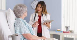 Docteur japonais tenant la tablette parlant à la femme mûre dans le lit d'hôpital Image stock