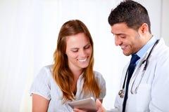Docteur latin et un patient regardant pour marquer sur tablette le PC Images libres de droits