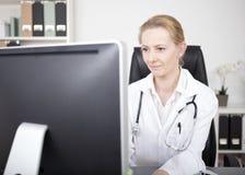 Docteur Looking de femme au moniteur d'ordinateur sérieusement Photo libre de droits