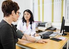Docteur Looking At Patient tout en examinant sa tension artérielle Photos stock