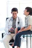 Docteur mâle confiant contrôlant le réflexe d'un patient image stock