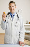 Docteur mâle donnant la bouteille de médicament Image stock