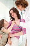 Docteur mûr examinant l'enfant heureux, souriant. Image libre de droits