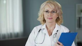 Docteur mûr examinant la garantie d'appareil-photo de haute qualité des services médicaux banque de vidéos