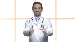 Docteur mûr heureux montrant deux pouces  banque de vidéos