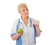 Docteur mûr avec la pomme et les pilules Photo libre de droits