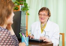 Docteur mûr derrière l'ordinateur avec le patient Image libre de droits
