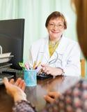 Docteur mûr derrière l'ordinateur avec le patient Photo libre de droits