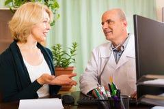 Docteur mûr parlant avec le patient féminin âgé photographie stock libre de droits