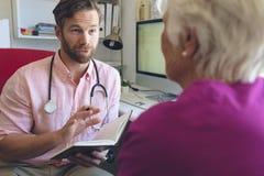 Docteur masculin écrivant la prescription à la femme supérieure dans la clinique photographie stock