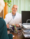 Docteur masculin amical discutant avec le patient féminin Image stock