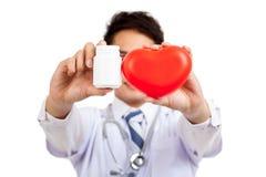 Docteur masculin asiatique avec la bouteille rouge de coeur et de pilule Image stock