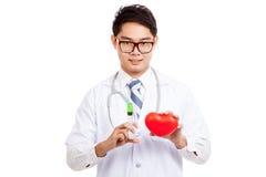 Docteur masculin asiatique avec la seringue et le coeur rouge Images libres de droits