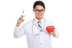Docteur masculin asiatique avec la seringue et le coeur rouge Photos libres de droits