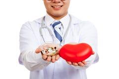 Docteur masculin asiatique avec le coeur et les pilules rouges Photos stock