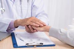 Docteur masculin attirant serrant la main du ` un s de patient dans son bureau Images stock