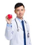 Docteur masculin avec la boule de forme de coeur Photographie stock