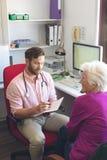 Docteur masculin ?crivant la prescription ? la femme sup?rieure dans la clinique photo stock