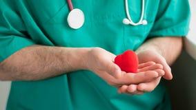 Docteur masculin dans le costume vert avec des prises de stéthoscope au coeur rouge lumineux de mains Horizontal, soins de santé, photographie stock
